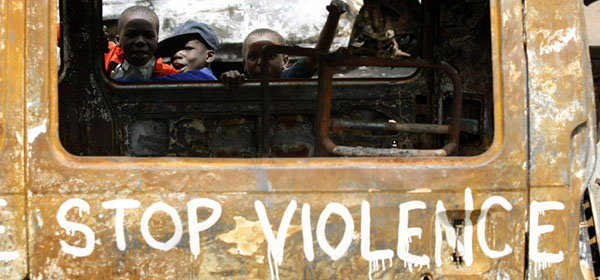 Children play next to a vehicle destroyed during post-election violence in Nairobi's Kibera slum